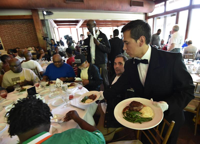 A waiter serves meals as Chinese philanthropist Chen Guangbiao hosts a lunch for 250 homeless people on June 25, 2014 at The Boathouse restaurant in New York's Central Park (AFP Photo/STAN HONDA)