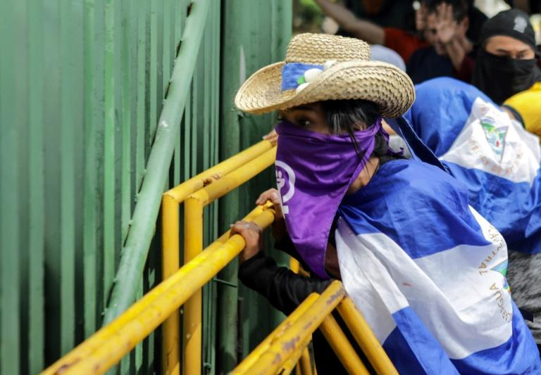 Protesters demonstrate in front of a police line at the Central American University in Managua on November 19