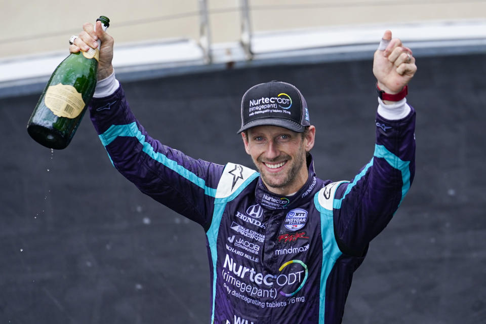 File-This May 15, 2021, file photo shows Romain Grosjean, of Switzerland, celebrating after finishing second in an IndyCar auto race at Indianapolis Motor Speedway in Indianapolis. Grosjean turned in his key to Indianapolis Motor Speedway — yes, he had his own key to the place — packed up his motorhome and headed out Tuesday toward Detroit for his next United States adventure. The man who walked through fire and lived to tell about has fully embraced his move from Formula One to IndyCar, where he won the pole in his third career start then led 44 laps on the road course at Indianapolis before finishing second. (AP Photo/Michael Conroy, File)