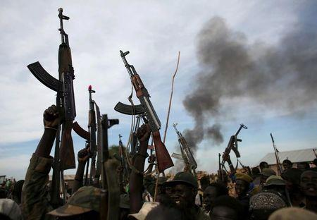 FILE PHOTO: Rebel fighters hold up their rifles as they walk in front of a bushfire in a rebel-controlled territory in Upper Nile State