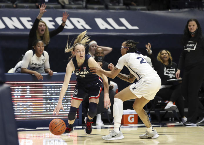 Connecticut guard Paige Bueckers (5) drives against Xavier forward A'Riana Gray (21) during the first half of an NCAA college basketball game Saturday, Feb. 20, 2021, in Cincinnati. (AP Photo/Gary Landers)