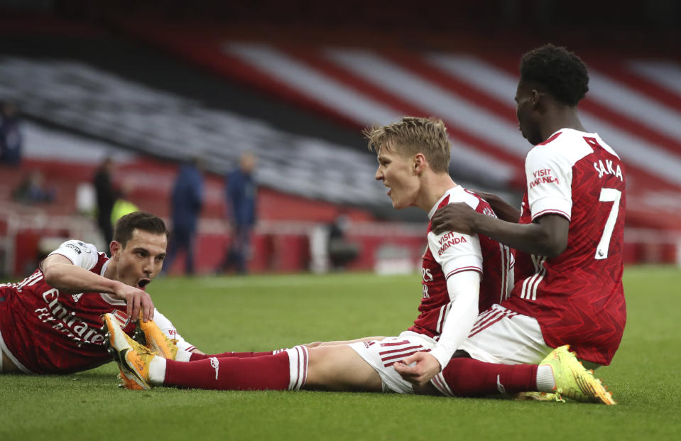 Arsenal's Martin Odegaard, centre, celebrates after scoring his side's opening goal during the English Premier League soccer match between Arsenal and Tottenham Hotspur at the Emirates stadium in London, England, Sunday, March 14, 2021. (Nick Potts/Pool via AP)
