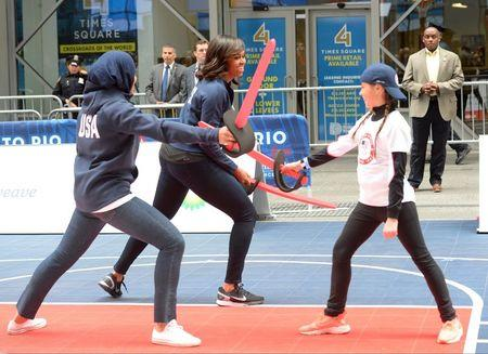 Apr 27, 2016; New York, NY, USA; First Lady Michelle Obama and fencer Ibithaj Muhammadin participate in a fencing demonstration during the U.S. Olympic Committee 100 day countdown event to the Rio 2016 Games at Times Square. Mandatory Credit: Robert Deutsch-USA TODAY Sports
