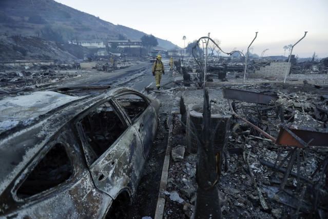 <p>Fire crews search for hot spots among destroyed homes in the Rancho Monserate Country Club community Friday, Dec. 8, 2017, in Fallbrook, Calif. (Photo: Gregory Bull/AP) </p>