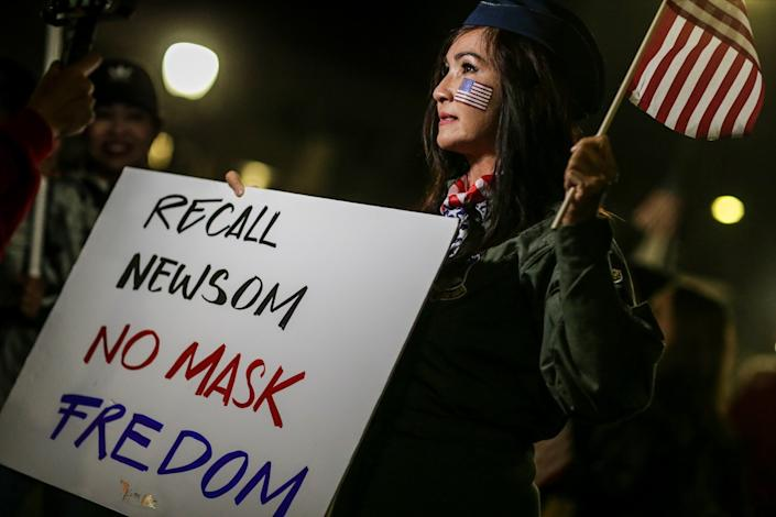 """A woman holds a sign reading """"Recall Newsom No Mask Fredom"""" [sic]"""