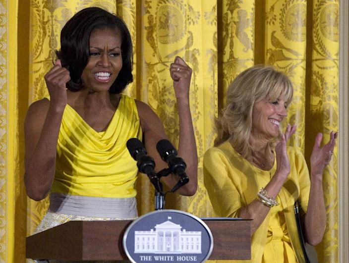 """FILE - In this May 10, 2012, file photo, first lady Michelle Obama, accompanied by Jill Biden speaks at a Joining Forces event in honor of military mothers in the East Room of the White House in Washington. Michelle Obama has a new look, both in person and online, and with the president's re-election, she has four more years as first lady, too. The first lady is trying to figure out what comes next for this self-described """"mom in chief"""" who also is a champion of healthier eating, an advocate for military families, a fitness buff and the best-selling author of a book about her White House garden. For certain, she'll press ahead with her well-publicized efforts to reduce childhood obesity and rally the country around its service members. (AP Photo/Carolyn Kaster, File)"""