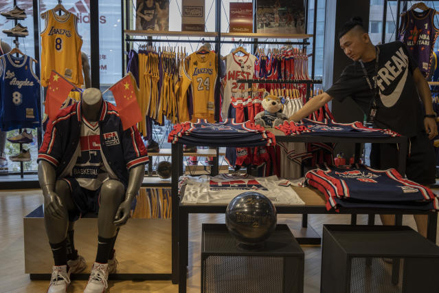 "In this Friday, Oct. 11, 2019, photo, a sales person adjust a mascot doll at a NBA merchandise store in Beijing. When Houston Rockets' general manager Daryl Morey tweeted last week in support of anti-government protests in Hong Kong, everything changed for NBA fans in China. A new chant flooded Chinese sports forums: ""I can live without basketball, but I can't live without my motherland.""(AP Photo/Ng Han Guan)"