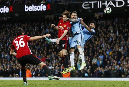 Britain Soccer Football - Manchester City v Manchester United - Premier League - Etihad Stadium - 27/4/17 Manchester City's Sergio Aguero and Nicolas Otamendi in action with Manchester United's Daley Blind  Action Images via Reuters / Jason Cairnduff Livepic