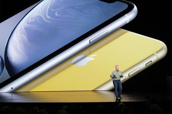 Apple exec Phil Schiller standing in front of an image of the new iPhone Xr devices..