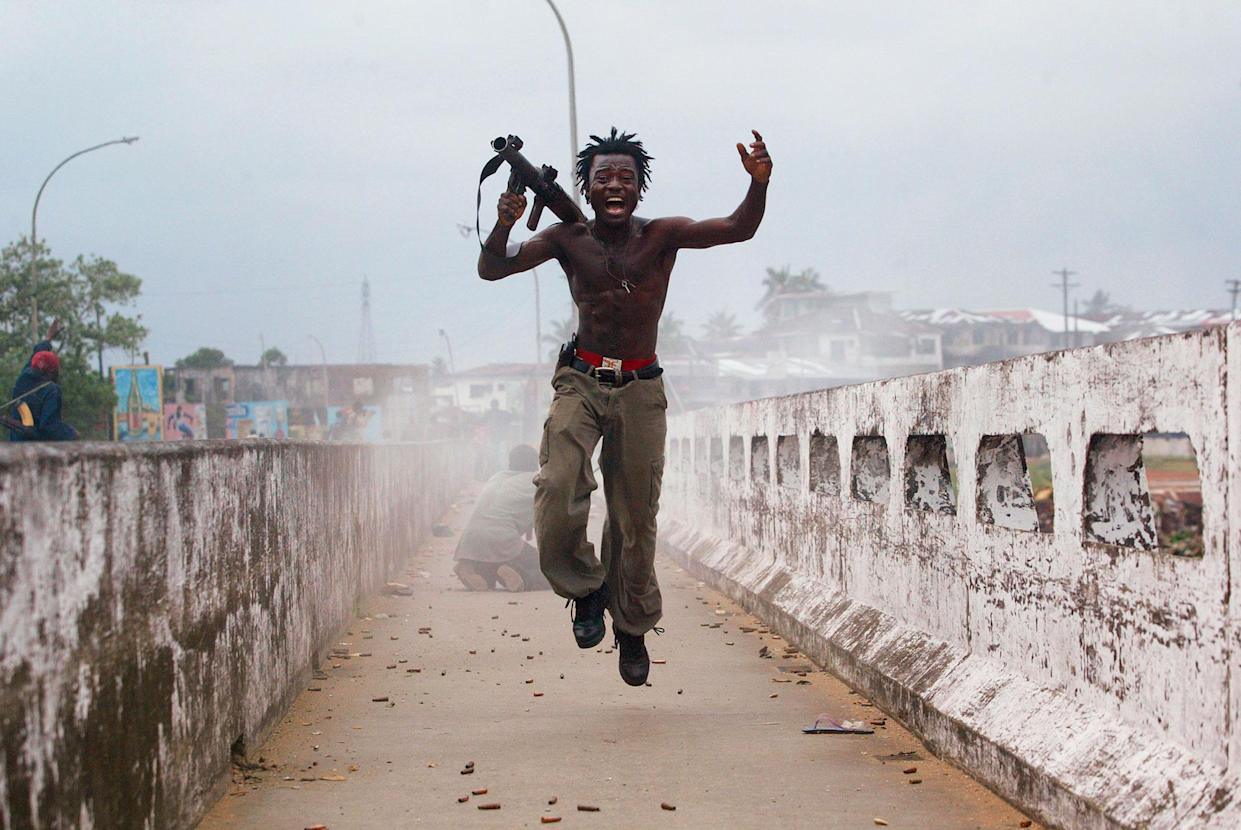 Joseph Duo, a Liberian militia commander loyal to the government, exults after firing a rocket-propelled grenade at rebel forces at a key strategic bridge on July 20, 2003, in Monrovia, Liberia. (Photo: Chris Hondros/Getty Images)