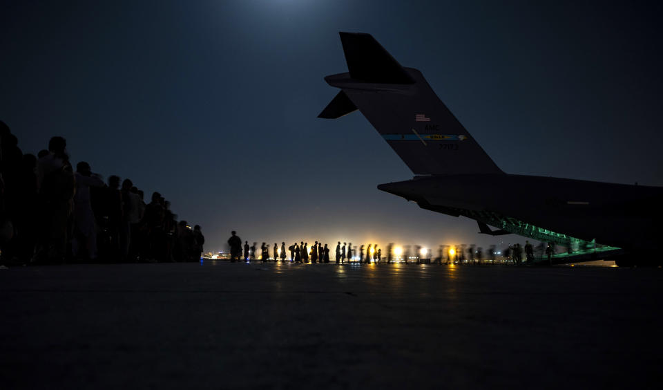 FILE - In this Saturday, Aug. 21, 2021 photo provided by the U.S. Air Force, aircrew assigned to the 816th Expeditionary Airlift Squadron assist qualified evacuees boarding a U.S. Air Force C-17 Globemaster III aircraft in support of the Afghanistan evacuation at Hamid Karzai International Airport, Kabul, Afghanistan. (Senior Airman Taylor Crul/U.S. Air Force via AP, File)