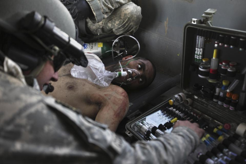 Airborne in a U.S. Army Task Force Pegasus helicopter, U.S. Army Staff Sgt. and flight medic Robert B. Cowdrey, of La Junta, Colo., gives medical care to an Afghan National Army soldier with a gunshot wound, during a medevac mission over Marjah, Helmand province, Afghanistan, Wednesday, Feb. 17, 2010. (AP Photo/Brennan Linsley)