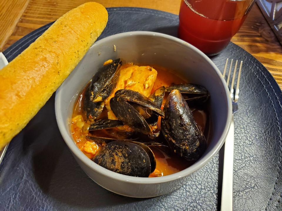 bowl of stew with clams and a side of bread
