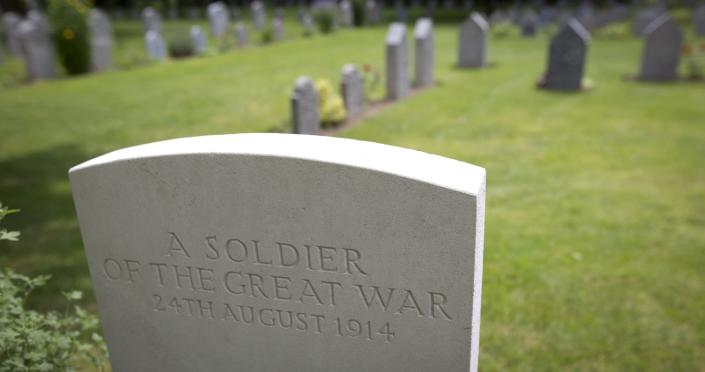"""FILE - In this In this Saturday, July 26, 2014 file photo the grave of an unknown Commonwealth World War I soldier, foreground, and German soldiers graves, background, at the St. Symphorien Cemetery near Mons, Belgium. The Commonwealth War Graves Commission has apologized after an investigation found that at least 161,000 mostly African and Indian men who died fighting for the British Empire during World War I weren't properly honored due to """"pervasive racism."""" The investigation found that at least 116,000 people, and possibly as many as 350,000, were either not commemorated by name or weren't commemorated at all, according to findings released Thursday, April 22, 2021. (AP Photo/Virginia Mayo, File)"""