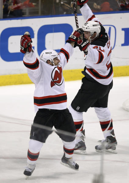 New Jersey Devils' Stephen Gionta, left,and Ryan Carter (20) celebrate after Gionta scored a goal against the Florida Panthers during the second period of Game 7 in a first-round NHL Stanley Cup playoff hockey series, in Sunrise, Fla., Wednesday, April 26, 2012. (AP Photo/J Pat Carter)