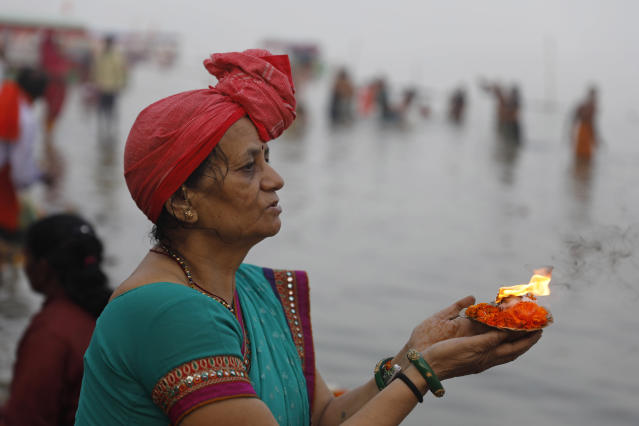A Hindu pilgrim offers prayers by the River Sarayu in Ayodhya, India , Saturday, Nov. 9, 2019. India's security forces were on high alert ahead of the Supreme Court's verdict Saturday in a decades-old land title dispute between Muslims and Hindus over plans to build a Hindu temple on a site where Hindu hard-liners demolished a 16th century mosque in 1992, sparking deadly religious riots. (AP Photo/Rajesh Kumar Singh)
