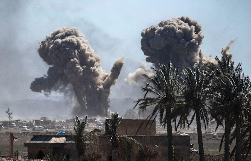 A plume of black smoke rises above the Islamic State group's last redoubt in the village of Baghouz in eastern Syria