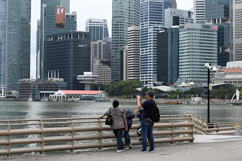 A man takes a photo as the financial business district looms in the background in Singapore on January 2, 2020. - Singapore's trade-reliant economy grew 0.8 percent in the fourth quarter to December, according to advance estimates by the trade ministry on January 2. (Photo by Roslan RAHMAN / AFP) (Photo by ROSLAN RAHMAN/AFP via Getty Images)