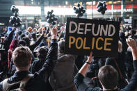 """FILE - In this Wednesday, Oct. 14, 2020, file photo, a protester holds a sign that reads """"Defund Police"""" during a rally for the late George Floyd outside Barclays Center, in New York. Demonstrators gathered on what would have been Floyd's 47th birthday to call for action in correcting systemic racism in policing and for criminal justice reform. Responses to the coronavirus pandemic and police brutality dominated legislative sessions in 2020 and led to many new laws that will take effect in the new year. (AP Photo/John Minchillo, File)"""