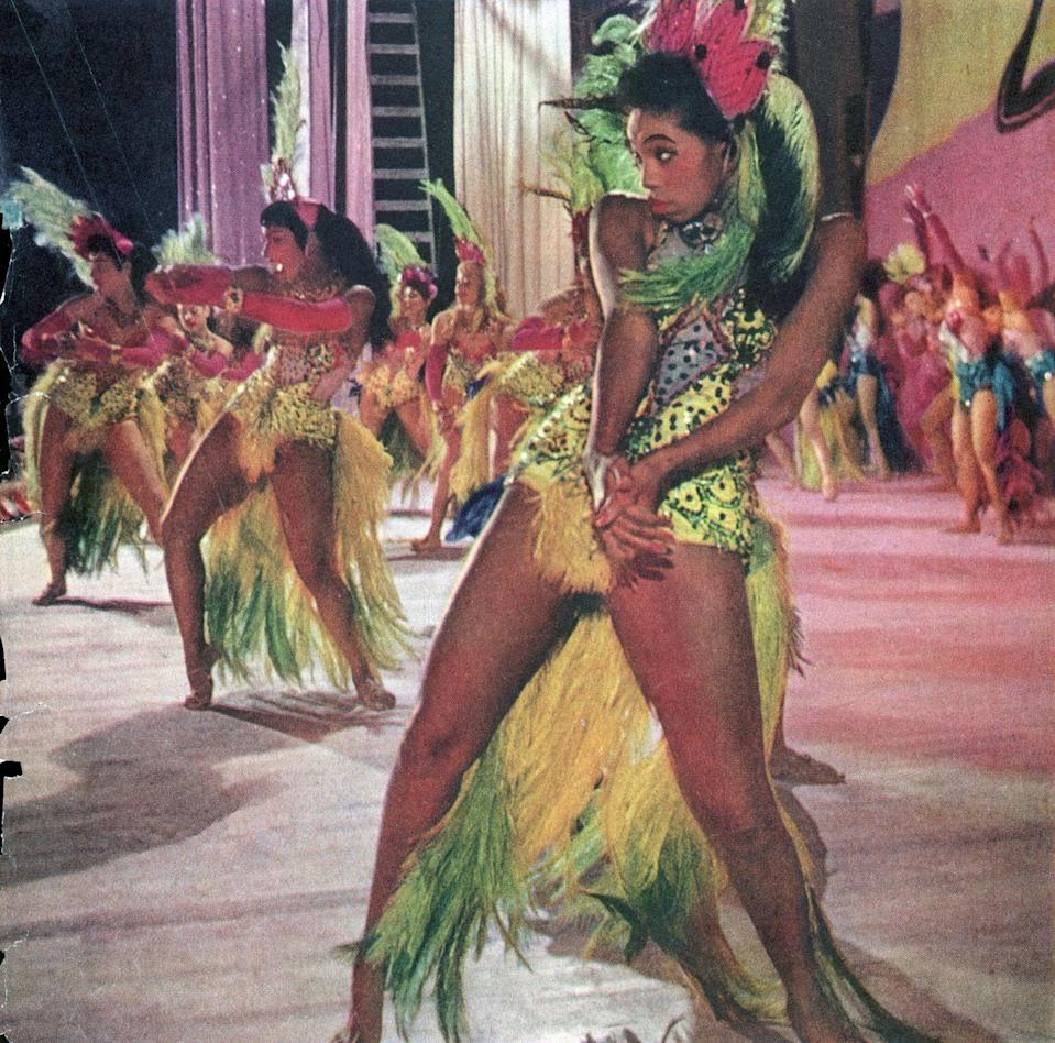 <p>Showgirls dressed in colorful sequins and feathered corsets perform at the Moulin Rouge in 1955. </p>