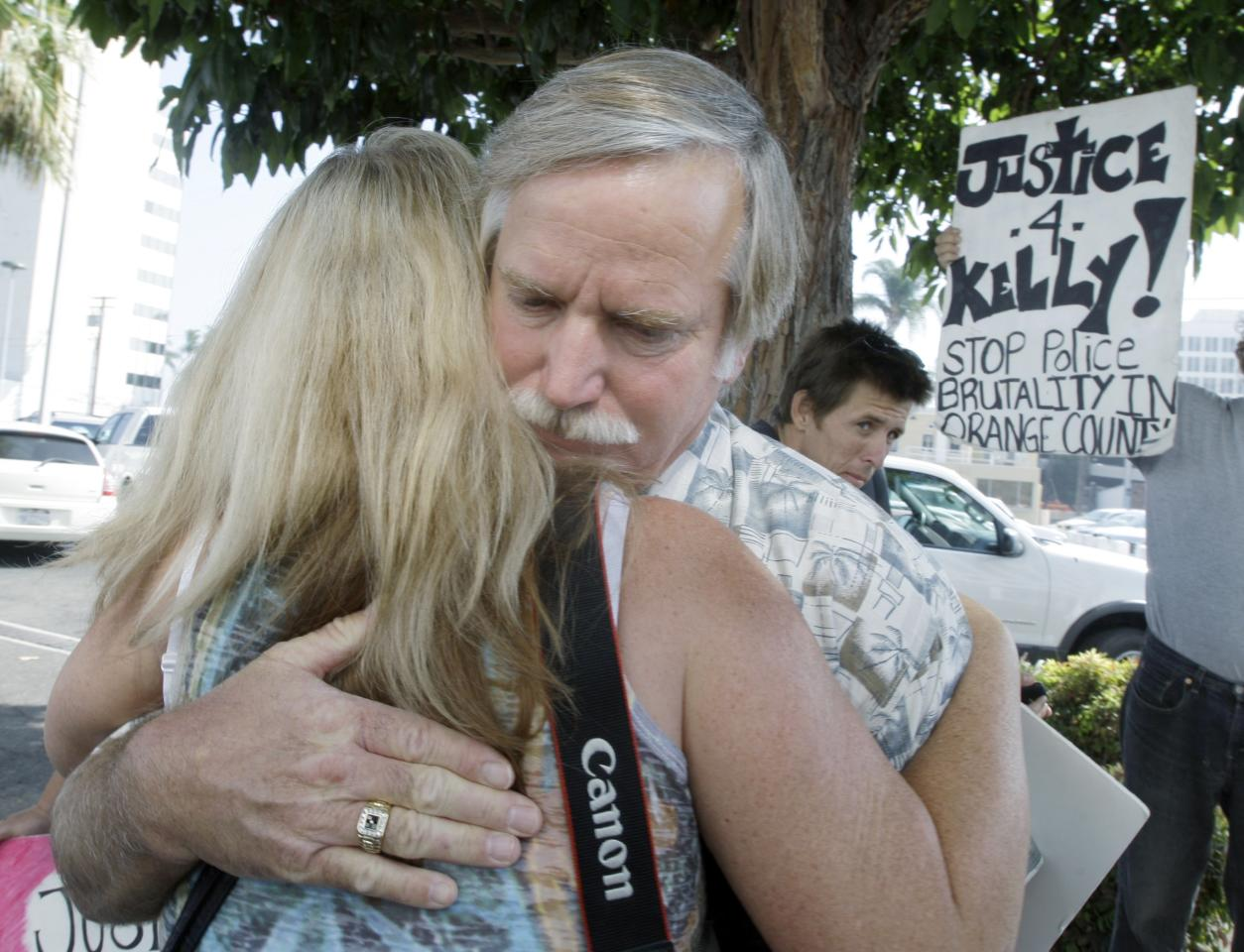 Ron Thomas, father of Kelly Thomas, embraces a supporter before Orange County, Calif., District Attorney Tony Rackauckas announces that two police officers will be charged in the death of his son, Kelly Thomas, a mentally ill homeless man, at a news conference in Santa Ana, Calif., Wednesday, Sept. 21, 2011. Fullerton, Calif., police officer Manuel Ramos was charged with one count each of second degree murder and involuntary manslaughter in the death of Thomas after a violent confrontation on July 5 with police officers. Police Cpl. Jay Cicinelli was charged with one count each of involuntary manslaughter and excessive force. (AP Photo/Reed Saxon)