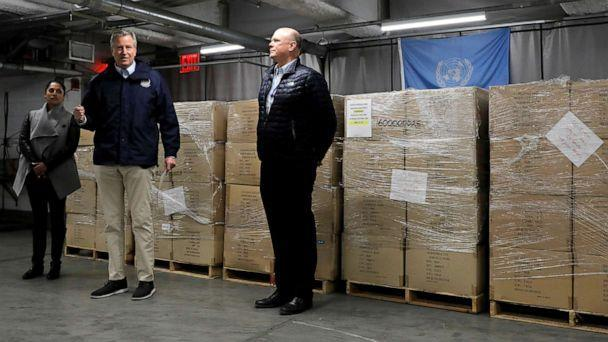 PHOTO: New York City Mayor Bill de Blasio, in the center, speaks to the media and accepts 250,000 face masks donated by the United Nations to urban health workers to help with the COVID-19 pandemic at UN headquarters in New York Help City on March 28, 2020 (Andrew Kelly / Reuters)