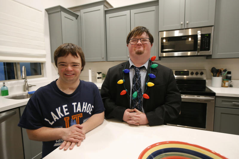In this Monday, Dec. 9, 2019, photo, Luke Humble, left, and Conor Gunderson, right, pose for a photograph in their kitchen in their home at the new Luna Azul housing development, in Phoenix. Humble and Gunderson, who have been buddies for five years, both have Down syndrome. They are among the first residents of Luna Azul, the latest example of housing developments for adults with disabilities spearheaded by their greatest advocates: their parents. (AP Photo/Ross D. Franklin)