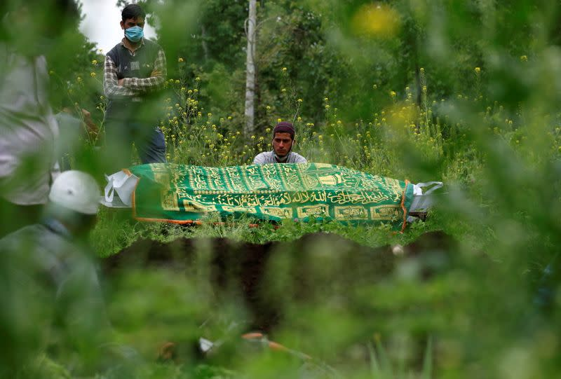 Relatives are seen next to the body of a man who died due to the coronavirus disease (COVID-19), as they wait for a grave to be prepared for his burial at a graveyard on the outskirts of Srinagar