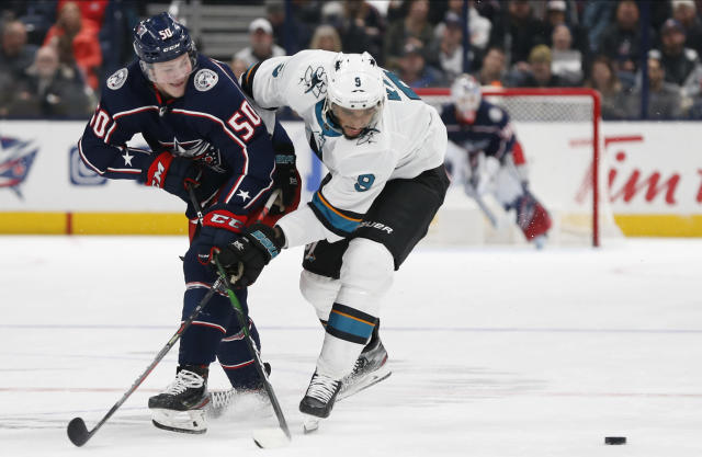 Columbus Blue Jackets' Eric Robinson, left, passes the puck in front of San Jose Sharks' Evander Kane during the second period of an NHL hockey game Saturday, Jan. 4, 2020, in Columbus, Ohio. (AP Photo/Jay LaPrete)