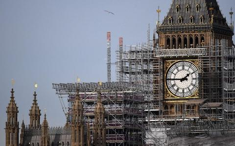 A bird flying in front of scaffolding around the Elizabeth Tower, commonly called Big Ben