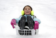 Peyton McKinney uses a laundry basket for a sled Monday, Feb. 15, 2021, in Nolensville, Tenn. Much of Tennessee was hit with a winter storm that brought freezing rain, snow, sleet and freezing temperatures. (AP Photo/Mark Humphrey)