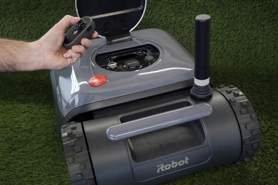 This Wednesday, Jan. 16, 2019 photo shows an iRobot Terra lawn mower with remote controller in Bedford, Mass. Cutting lawns seemed a logical next step for an inventor of home robots trying to upend routine domestic chores. But navigating around a typical American yard without destroying its flowerbeds was harder than it seemed. (AP Photo/Elise Amendola)
