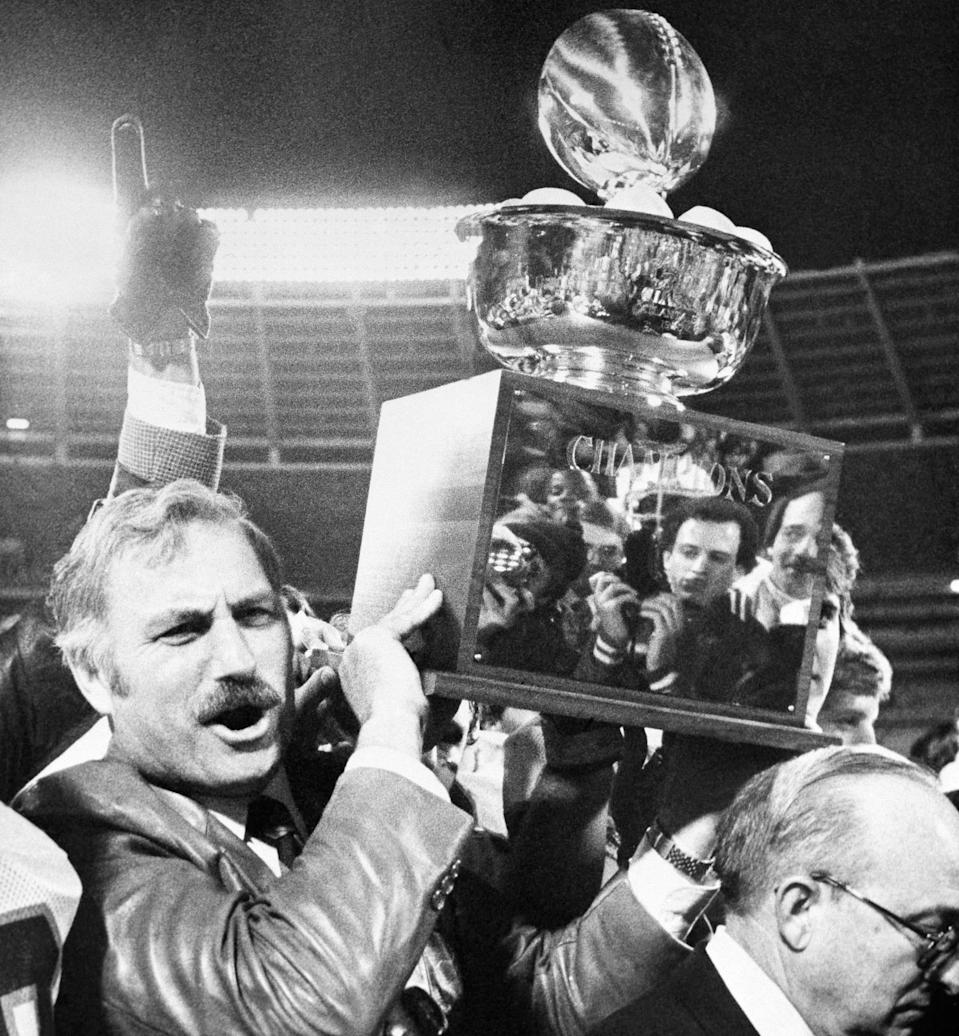 University of Miami coach Howard Schnellenberger holds the 1981 Peach Bowl trophy aloft after his team defeated Virginia Tech. (AP Photo/Joe Sebo)