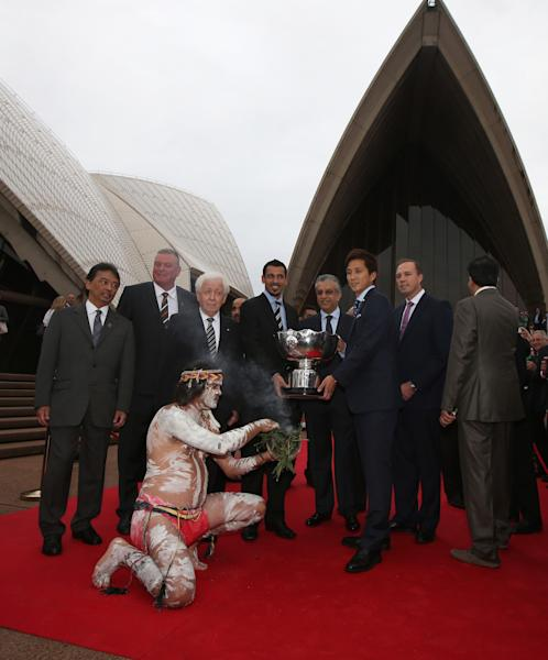 Aboriginal man Glen Doyle, kneeling at center, from the Muruwuri clan, performs a traditional smoking ceremony as the Asian Cup trophy arrives at the Sydney Opera House before the Asian Football Confederation draw for the 2015 Asian Cup in Sydney, Wednesday, March 26, 2014. Australia hosts the tournament that will be played in Jan. 2015. (AP Photo/Rick Rycroft)