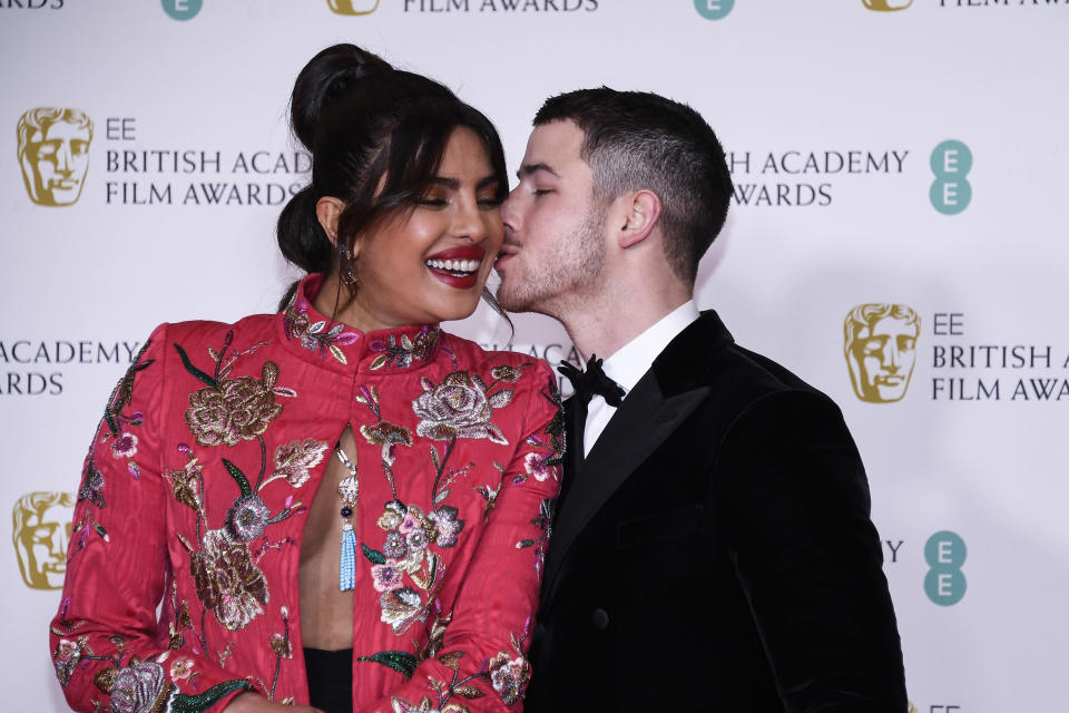 Actress Priyanka Chopra Jonas, left, is kissed by her husband singer Nick Jonas upon arrival at the Bafta Film Awards, in central London, Sunday, April 11 2021. (AP Photo/Alberto Pezzali)
