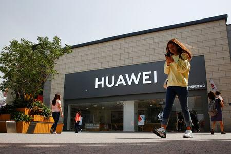 A woman looks at her phone as she walks past a Huawei shop in Beijing, China May 16, 2019.  REUTERS/Thomas Peter