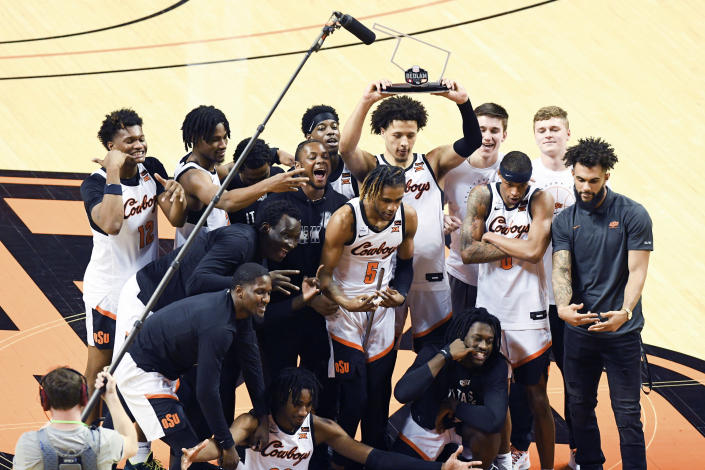 Oklahoma State guard Cade Cunningham holds the Bedlam trophy above the team following their win over rival Oklahoma in an NCAA college basketball game Monday, March 1, 2021, in Stillwater, Okla. (AP Photo/Brody Schmidt)