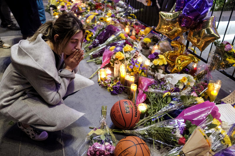 A fan pays her respects at a memorial for Kobe Bryant near Staples Center, Monday, Jan. 27, 2020, in Los Angeles. Bryant, the 18-time NBA All-Star who won five championships and became one of the greatest basketball players of his generation during a 20-year career with the Los Angeles Lakers, died in a helicopter crash Sunday. (AP Photo/Ringo H.W. Chiu)