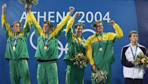 <p>Michael Phelps stands on the podium with his bronze medal as the relay team of South Africa celebrates winning gold in the men's swimming 4 x 100-meter freestyle relay final on August 15, 2004 in Athens. (Daniel Berehulak/Getty Images for FINA)</p>