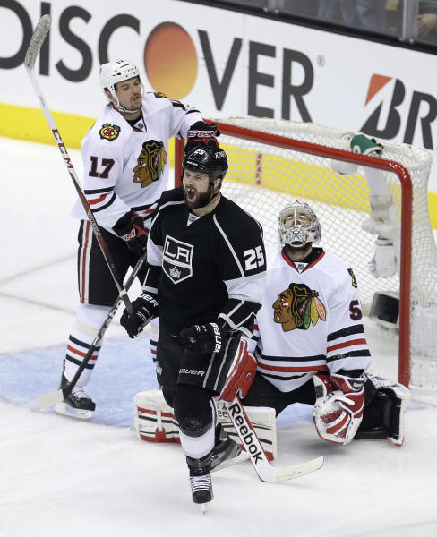 Los Angeles Kings left wing Dustin Penner, middle, celebrates his goal, in front ofChicago Blackhawks goalie Corey Crawford, right, and Sheldon Brookbank during the second period in Game 4 of the NHL hockey Stanley Cup playoffs Western Conference finals in Los Angeles, Thursday, June 6, 2013. (AP Photo/Chris Carlson)