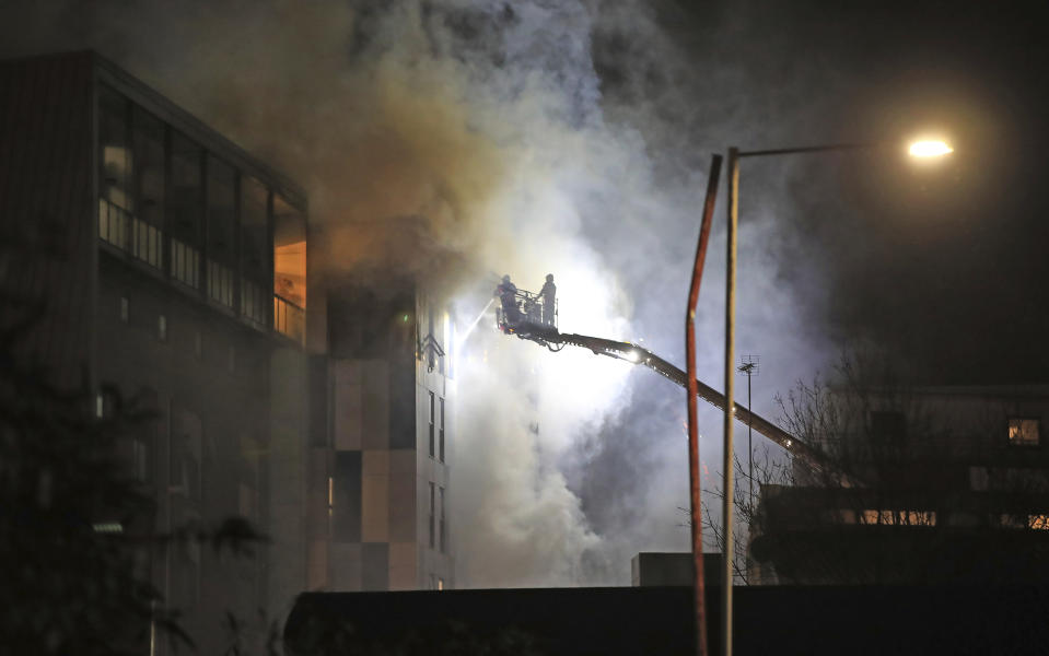 """Fire fighters work at the scene of a major fire at a student residential building in Bolton, England, late Friday Nov. 15, 2019.  Fire crews tackled the large blaze described by an eye witness as """"crawling up the cladding"""" of a student accommodation building, with students evacuated but still being accounted for Saturday morning. (Peter Byrne/PA via AP)"""