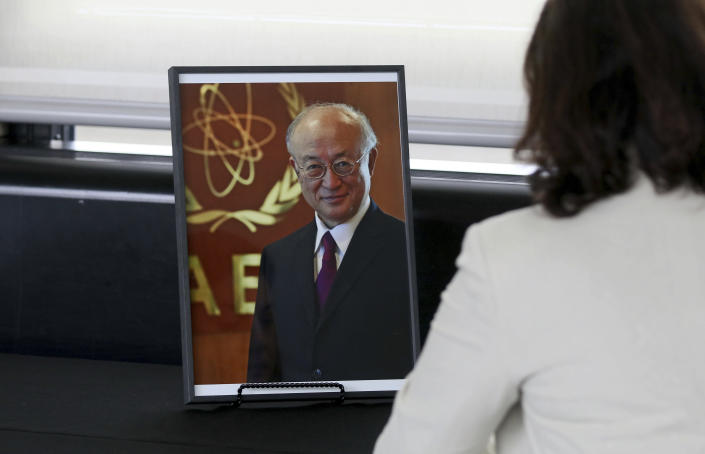An employee signs a book of condolence in front a photo of Director General of the International Atomic Energy Agency, IAEA, Yukiya Amano from Japan in Vienna, Austria, Monday, July 22, 2019. The IAEA announced the death of the agency's Director General Yukiya Amano at the age of 72 years. (AP Photo/Ronald Zak)