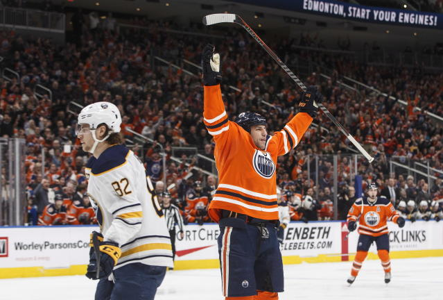 Buffalo Sabres' Nathan Beaulieu (82) skates past as Edmonton Oilers' Milan Lucic (27) celebrates a goal during second period NHL hockey action in Edmonton, Alberta, on Monday, Jan. 14, 2019. (Jason Franson/The Canadian Press via AP)