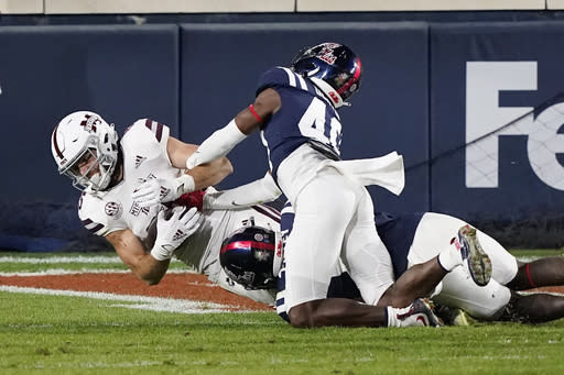 Mississippi State wide receiver Austin Williams (85) lunges past Mississippi defenders to catch a 7-yard touchdown pass during the second half of an NCAA college football game, Saturday, Nov. 28, 2020, in Oxford, Miss. (AP Photo/Rogelio V. Solis)