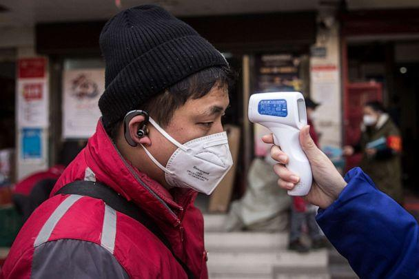 PHOTO: A community worker checks the temperature of courier in an Express station on January 29, 2020 in Hubei Province, Wuhan, China. (Getty Images)