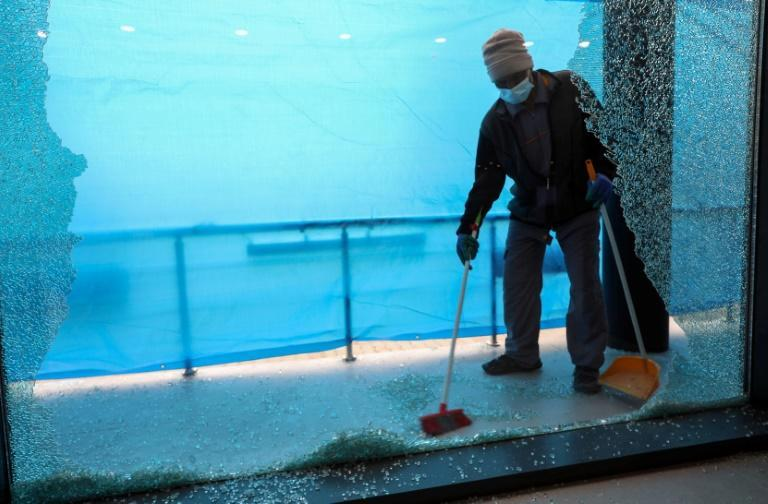 A worker clears shattered glass from a shopfront in the Kurdish regional capital Arbil, one of several civilian areas of the city to be hit in Monday night's rocket attack
