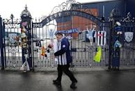 A fan walks away after leaving a tribute to Cyrille Regis at the Jeff Castle gates of West Bromwich Albion football club's The Hawthorns stadium in West Bromwich, Britain January 15, 2018. REUTERS/Darren Staples