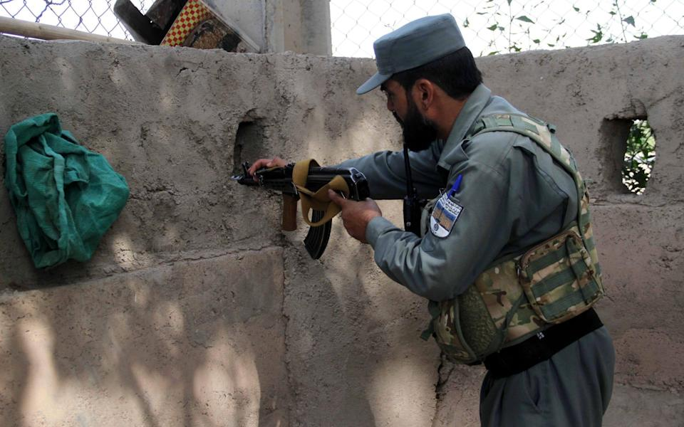 An Afghan security official stand guard outside the UN office in Herat