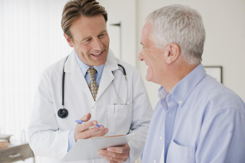 Doctor smiling while talking to older male