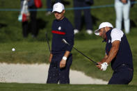 FILE - In this Sept. 25, 2018, file photo, the United States' Jordan Spieth,left, watches as Dustin Johnson plays from a bunker on the third hole during practice at the Ryder Cup golf matches at Le Golf National in Guyancourt, outside Paris, France. The 2020 U.S. Ryder Cup team includes veterans Johnson and Spieth — the only Americans to have played at least three Ryder Cups. (AP Photo/Alastair Grant, File)